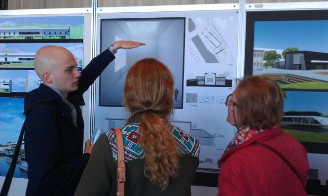 André Eriksson berättar om sitt förslag under minglet i utställningen